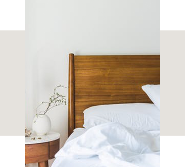 wooden bed frame with white sheets and pillows with a vase of flowers on the nightstand